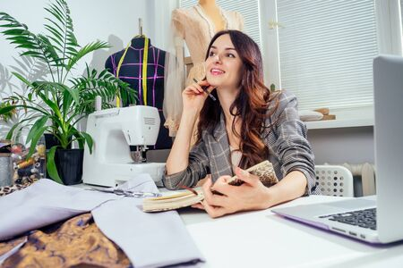 Young creative brunette woman in a cozy studio, startup of small tailoring business Standard-Bild