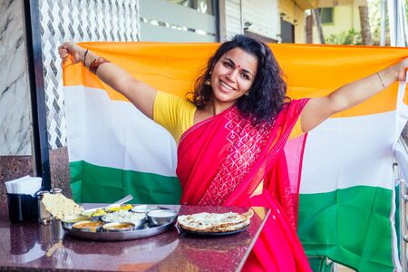 beautiful brunette woman in red sari holding big indian flag . traditional thali with rice,curd,dal on the table
