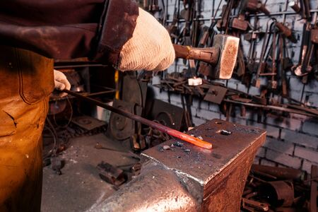 hammer industry small business concept.african american man dressed in historical clothing is hammering on the anvil. A blacksmith forges a metal product. Standard-Bild