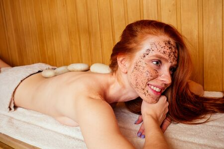 redhaired ginger young woman peeling face with brown sugar in traditional russian banya.steaming and self-care in finnish sauna taking stones massaging