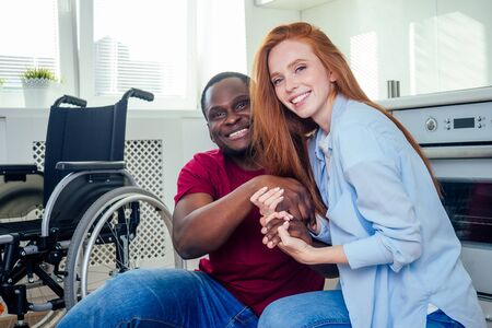 Young bearded handicapped african american man in wheelchair and his pretty wife at kichen