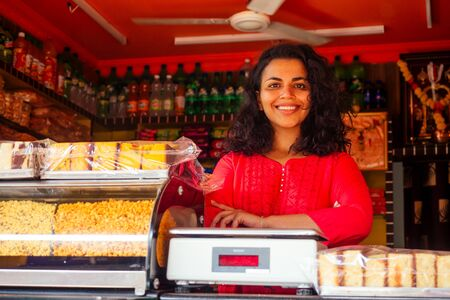 happy india saller female saling sweets in a local sweet shop gulab jamun in Goa