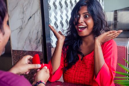 amased and surprised indian woman feeling happy to get proposal from her boyfriend in restaurant. i said yes Stock Photo