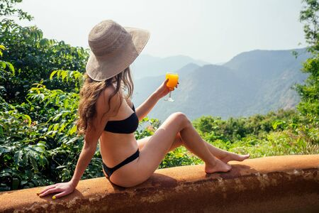 girl relaxing on inflatable pink donut in the infinity swimming pool at Goa india resort with coctail glass Stockfoto