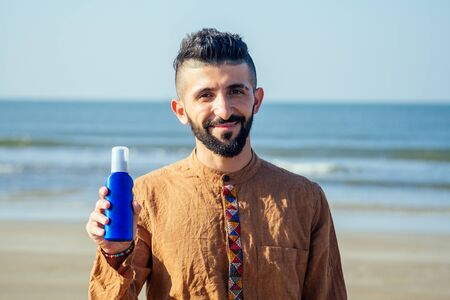 happy young arabian man useing sun cream protect on the beach.Indian male holding a bottle of sunscreen