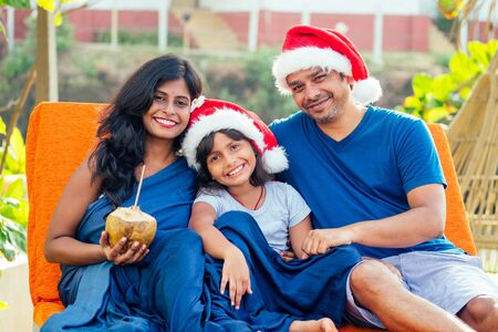 Happy Indian couple and daughter celebrating new year in tropical resort in Goa India.wearing santas hats