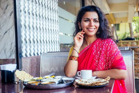 beautiful brunette woman in red sari eating with appetite traditional thali with rise,curd,dal in Goa restaurant and drinking masala tea Stockfoto
