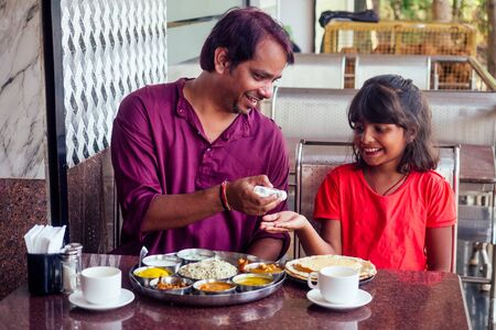 Father ,mother and little girl using wash hand sanitizer gel before eating in india cafe