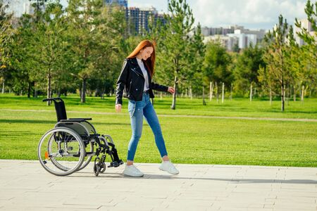 redhaired ginger woman making first steps after long recovery.she walking without her wheelchair in spring park Zdjęcie Seryjne