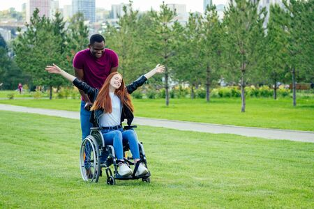 afro american man marriage proposal giving a ring to his redhaired ginger girlfriend.she sitting on wheel chair and surprised and amazed