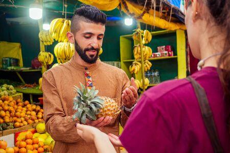 arabian man offering a pineapple on the street in goa Standard-Bild