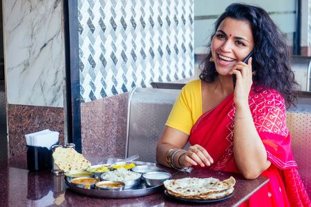 beautiful brunette woman in red sari eating with appetite traditional thali wirh rise,curd,dal in Goa restaurant masala tea. she talking by phone with show -white smile