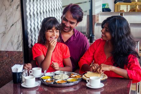 beautiful mother and happy father eating thali with daughter in cafe and drinking masala tea Stock Photo