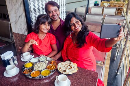 beautiful mother and happy father eating thali with daughter in cafe and drinking masala tea and making selfie photo on smartphone camera