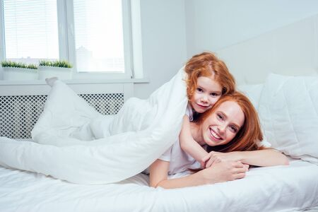 two happy redhaired ginger girls playing hide and seek under white blanket. self-isolation corona virus outbreak concept