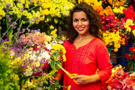 portrait of brunette indian florist female in floral bazar looking at camera and smile