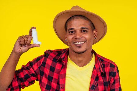 latin brazilian man using asthma inhaler at studio yellow background