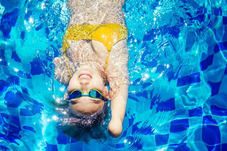 beautiful young armless woman training to swim in pool at tropical resort