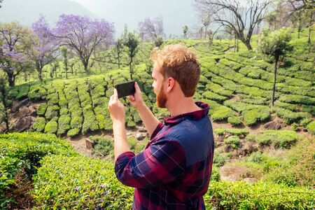 bloger redhaired ginger male enjoying morning taking selfie pictures on camera of smartphone in India chai plantations Munnar .
