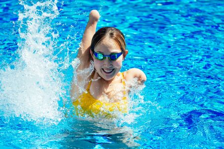 beautiful young armless woman training to swim in pool at tropical resort Stockfoto