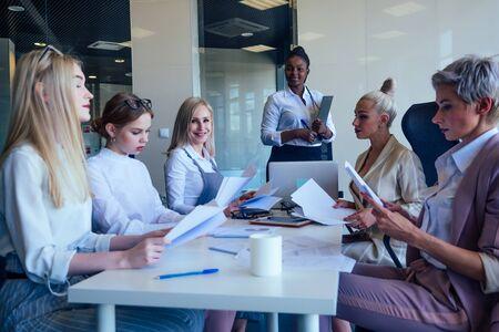 Diverse women applaud at modern centre business meeting.