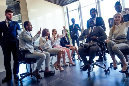 mixed race businesswoman and businessman raised game on riding chairs in the modern office panoramic window 스톡 콘텐츠