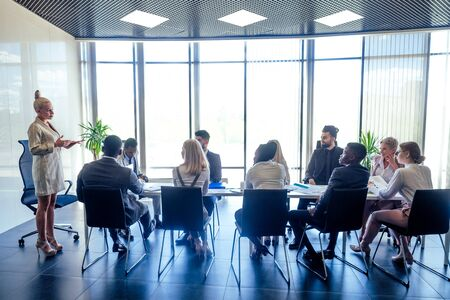 a group of successful afro americans, europeans ,arabic and korean businessman and businesswoman working in the office with large glass windows Stock Photo
