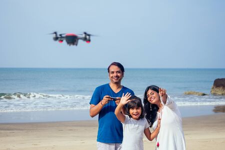 happy indian family are operating the drone by remote control in the beach in Goa