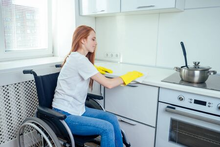 young redhaired ginger disabled woman in wheelchair wearing yellow ribon gloves and cleaning apartment