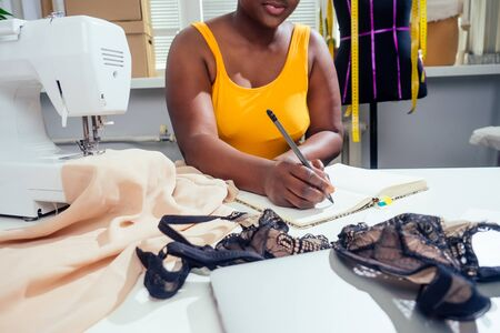 beautiful african american tailor woman sewing laces sexy lingerie in showroom Banco de Imagens
