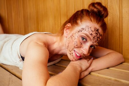 redhaired ginger young woman peeling face with brown sugar in traditional russian banya.steaming and self-care in finnish sauna