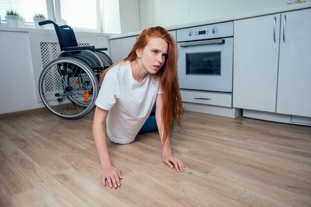 redhaired ginger woman falling down and crawling for help in kitchen room