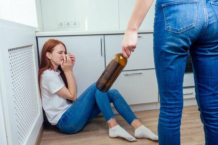 Violencia doméstica. Madre enojada golpeando a una adolescente con una botella de alcohol
