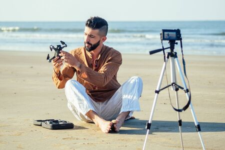 arabian man sitting on sand and talking tripod video making review of quadrocopter in beach. Travel videographer lifestyle content maker concept