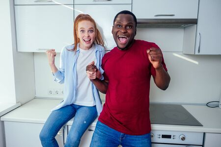 african american man and redhaired ginger woman dancing at kichen and feeling good mood.mixed race couple newlyweds
