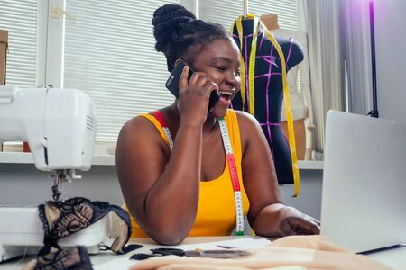 woman fashion designer with afro pigtails dreadlocks working on her home atelier
