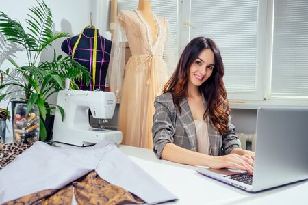 Young creative brunette woman in a cozy studio, startup of small tailoring business