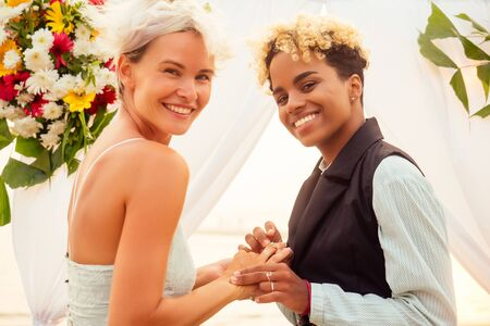 african american female groom in black suit and happy caucasian blonde bride loving together on beach ceremony under floral arch
