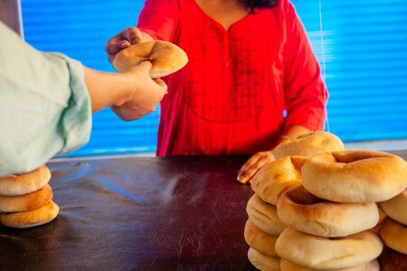 happy indian female salling fresh traditional buns in bazar Stock Photo