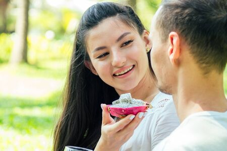 young indian woman in lace white boho dress having a dating with her boyfriend in summer park Stockfoto