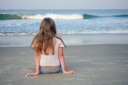 young girl sit on sand and looking at water .