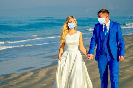 handsome groom in a chic suit and a beautiful bride in a wedding gown walk along the beach. concept of a chic and rich wedding ceremony on the beach