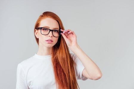 redhaired ginger woman wearing glasses and white cotton eco t-shirt in gray studio background