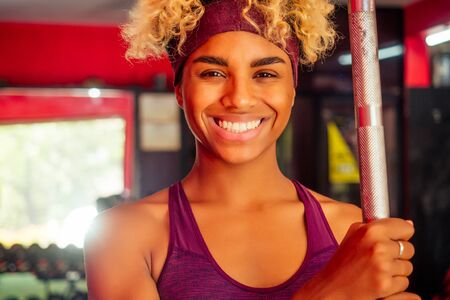sporty african american woman pull-up athletic iron indoors
