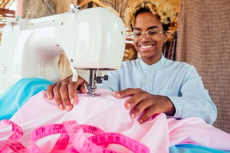 brazilian designer female with cute blonde afro curls hair making handmade clothes in her tropical eco house in Bali