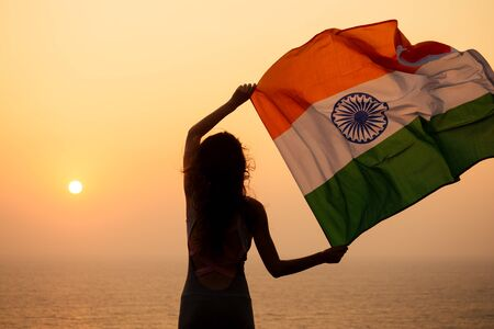 woman hjlding indian flag and looking at sunset Stock Photo
