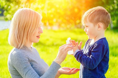 beautiful mother wipes her sons hands with wet hygienic napkins antibacterian sanitizer gel in the park in summer . anti bacterial napkins and freshness concept
