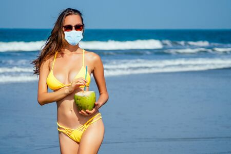 beautiful tanned girl in trendy yellow bathing suit sunglasses stands with coconut in her hands on beach tropical island vacation travel swimwear new season.derox diet idea 写真素材