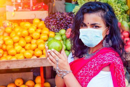 Portrait of beautiful traditional Indian woman in red sari dress choosing avocado fruits in a street Delhi market in india mumbai.Happy girl shopper in a supermarket fruit vegetable shop Kerala Goa. 写真素材