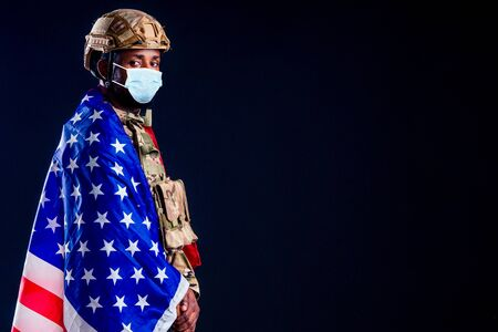military army african male camouflage suit sorrow wrapped in an American flag black background studio 写真素材